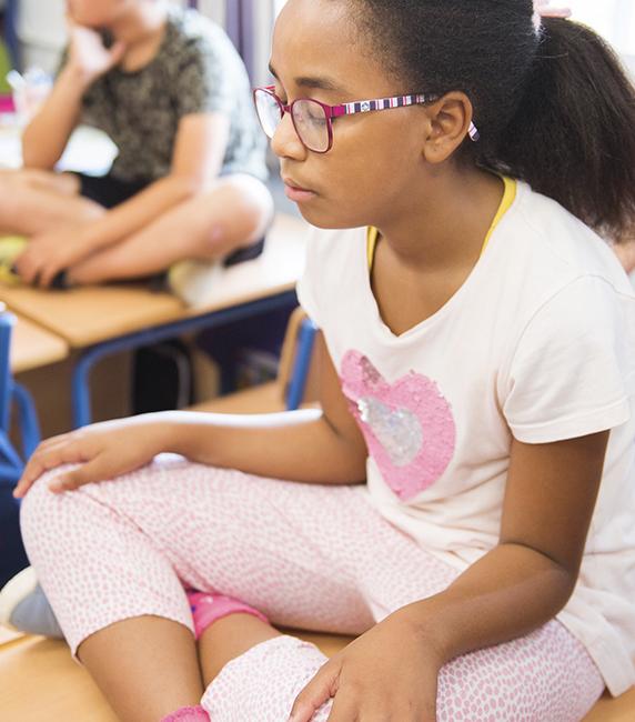 Niña practicando mindfulness en su escuela